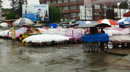 A lone fruit vendor longing for some customers on this rainy morning