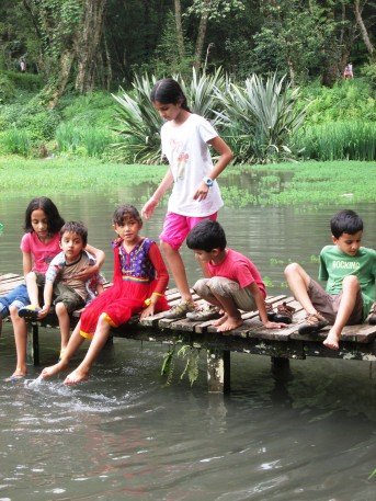 The children playing on a small pier leading to a temple in the middle of the pond.