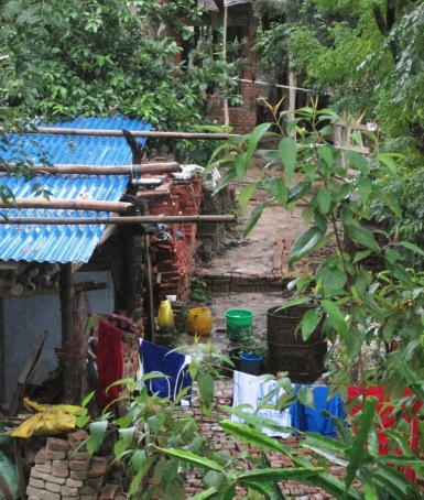 The outdoor washroom of our lower-income neighbors, with clothes drenched from last night's rain