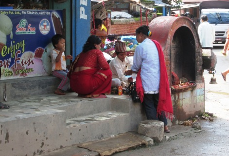 Here a young Nepali boy is offering blessings and a thread to those who approach him - perhaps he is in training to become a priest.