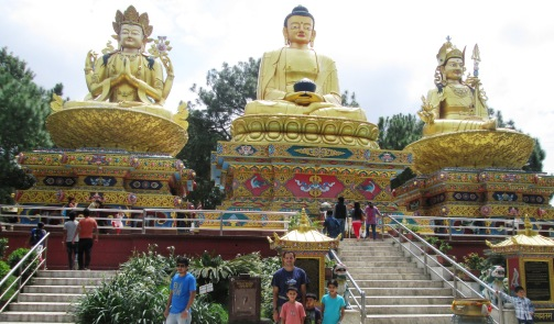 Prakash and the kids in front of 3 golden Buddha statues.