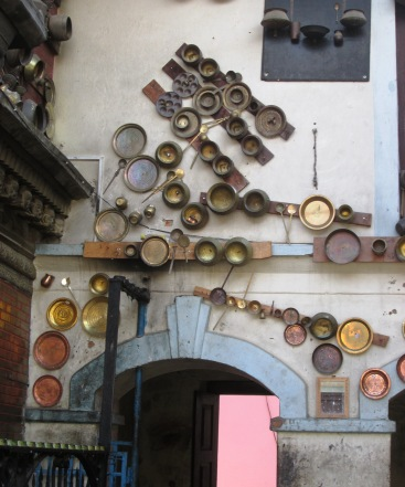The temple at the top of Chobar Hill has intriguing iron and brass decorations - a relatively costly kitchen item is given to the temple in the memory of recently deceased family member and nailed to the facade.  The tradition has been going on for years therefore thousands of plates, bowls, spoons, pots and other kitchen are visible.